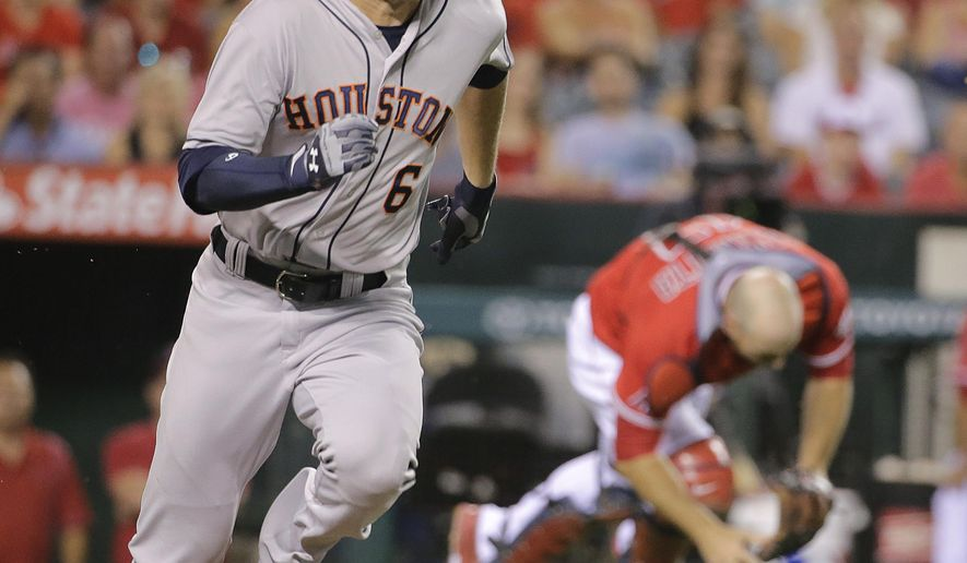 Houston Astros' Jake Marisnick runs to first base as Los Angeles Angels catcher Chris Iannetta, background right, loses the ball hit for a RBI single by Marisnick during the first inning of a baseball game Friday, Sept. 12, 2014, in Anaheim, Calif. (AP Photo/Jae C. Hong)
