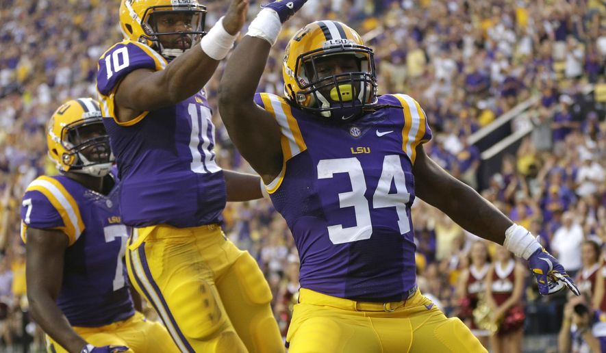 LSU running back Darrel Williams (34) celebrates his touchdown carry with quarterback Anthony Jennings (10) and running back Leonard Fournette (7) during the first half of an NCAA college football game against Louisiana-Monroe in Baton Rouge, La., Saturday, Sept. 13, 2014. (AP Photo/Gerald Herbert)