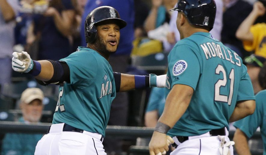 Seattle Mariners Robinson Cano, left, celebrates with Kendrys Morales, right, after Cano hit a solo home run in the first inning of a baseball game against the Oakland Athletics, Friday, Sept. 12, 2014, in Seattle. (AP Photo/Ted S. Warren)