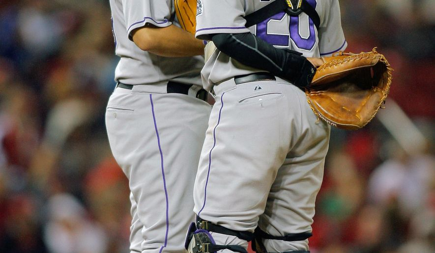 Colorado Rockies starting pitcher Jorge De La Rosa, left, listens to catcher Wilin Rosario as they meet on the mound during the fourth inning of a baseball game against the St. Louis Cardinals Friday, Sept. 12, 2014, in St. Louis. (AP Photo/Scott Kane)