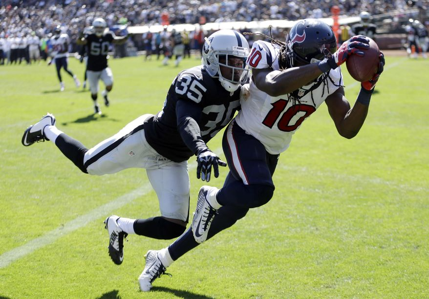 Houston Texans wide receiver DeAndre Hopkins, right, hauls in a 12-yard pass for a touchdown as Oakland Raiders defensive back Chimdi Chekwa, left, makes the tackle in the third quarter of an NFL football game Sunday, Sept. 14, 2014, in Oakland, Calif. (AP Photo/Ben Margot)
