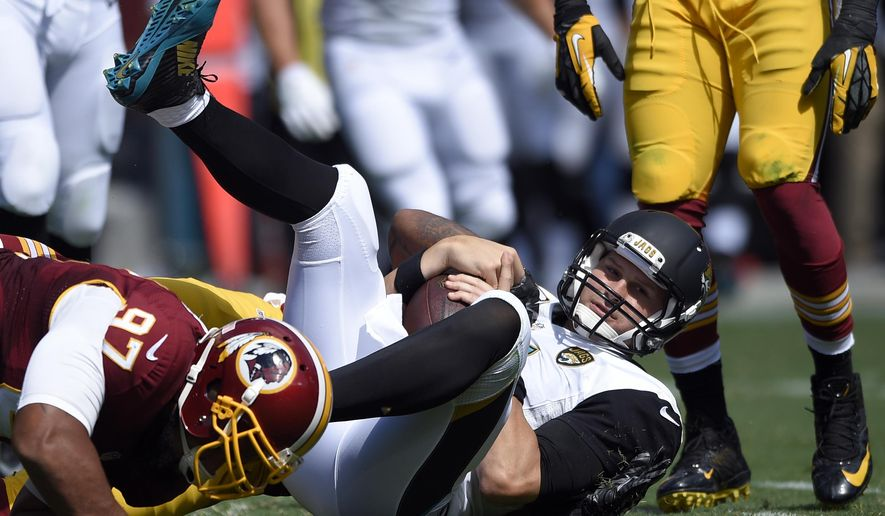 Jacksonville Jaguars quarterback Chad Henne is sacked by Washington Redskins inside linebacker Perry Riley (56) and defensive end Jason Hatcher (97), during the first half of an NFL football game Sunday, Sept. 14, 2014, in Landover, Md. (AP Photo/Nick Wass)