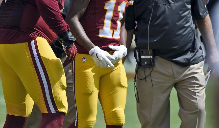 Washington Redskins wide receiver DeSean Jackson (11) is helped off the field after he was injured, by tackle Trent Williams (71) and head coach Jay Gruden, right, during the first half of an NFL football game against the Jacksonville Jaguars, Sunday, Sept. 14, 2014, in Landover, Md. (AP Photo/Nick Wass)
