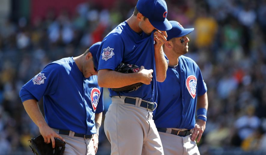 Chicago Cubs starting pitcher Jacob Turner, center, waits with second baseman Chris Valaika, left, and first baseman Mike Olt, for manager manager Rick Renteria during the fifth inning of a baseball game against the Pittsburgh Pirates in Pittsburgh, Sunday, Sept. 14, 2014. Renteria pulled Turner from the game.  (AP Photo/Gene J. Puskar)