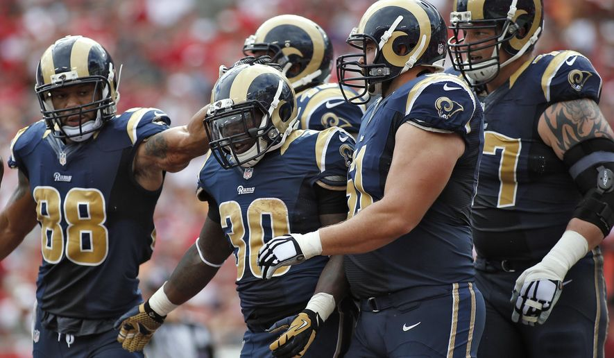 St. Louis Rams running back Zac Stacy (30) celebrates with teammates, including tight end Lance Kendricks (88) and center Tim Barnes (61), after scoring against the Tampa Bay Buccaneers during the first quarter of an NFL football game Sunday, Sept. 14, 2014, in Tampa, Fla. (AP Photo/Brian Blanco)