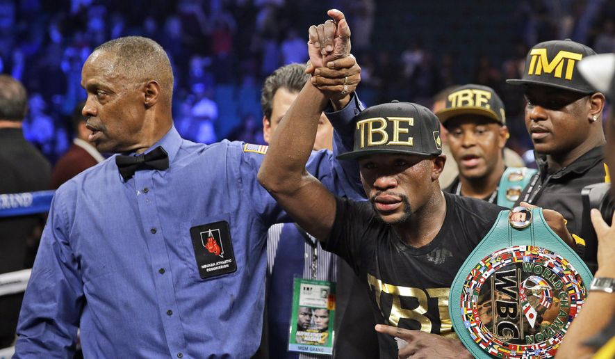 Floyd Mayweather shows off his belts after beating Marcos Maidana during their WBA welterweight and WBC super  welterweight title fight, Saturday, Sept. 13, 2014, in Las Vegas. (AP Photo/John Locher)