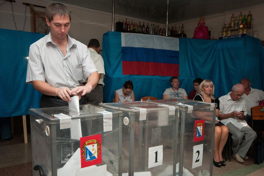 A man casts his ballot papers at a polling station set up in a cafe hall, with a Russian flag in the background, during regional parliament and municipal election in Sevastopol, Crimea, Sunday, Sept. 14, 2014. (AP Photo/Alexander Polegenko)