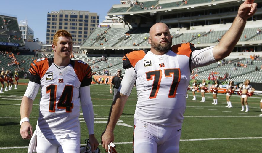 Cincinnati Bengals quarterback Andy Dalton (14) walks off the field with tackle Andrew Whitworth (77) after they defeated the Atlanta Falcons 24-10 in an NFL football game, Sunday, Sept. 14, 2014, in Cincinnati. (AP Photo/Michael Conroy)