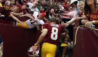 Washington Redskins quarterback Kirk Cousins (8) runs off the field after an NFL football game against the Jacksonville Jaguars on Sunday, Sept. 14, 2014, in Landover, Md. The Redskins won 41-10. (AP Photo/Evan Vucci)