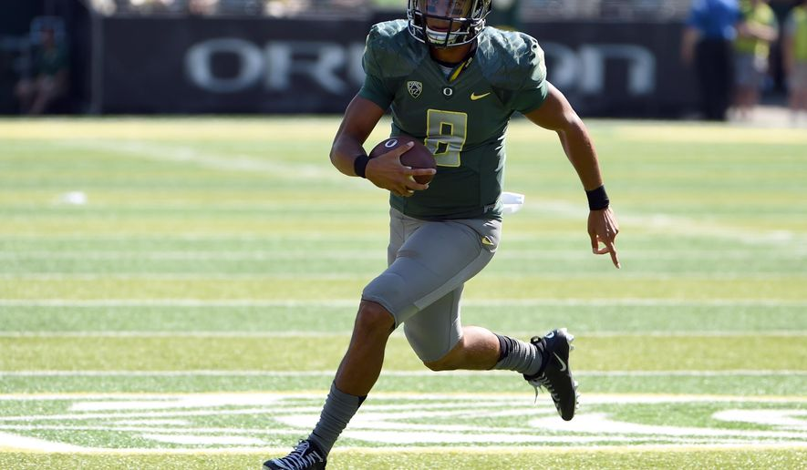 Oregon quarterback Marcus Mariota (8) runs the ball in for a touchdown during the second quarter of an NCAA college football game against Wyoming at Autzen Stadium on Saturday, Sept. 13, 2014, in Eugene, Ore. (AP Photo/Steve Dykes)