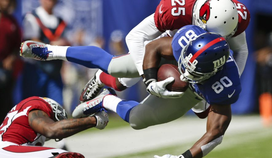 Arizona Cardinals cornerback Jerraud Powers (25) tackles New York Giants wide receiver Victor Cruz (80) during the first half of an NFL football game Sunday, Sept. 14, 2014, in East Rutherford, N.J.  (AP Photo/Kathy Willens)