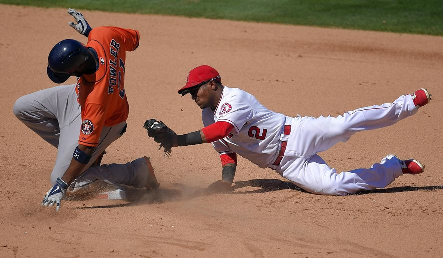Los Angeles Angels shortstop Erick Aybar, right, dives in an attempt to tag out Houston Astros' Dexter Fowler as Fowler slides in for a double during the sixth inning of a baseball game, Sunday Sept. 14, 2014, in Anaheim, Calif. The Astros won 6-1. (AP Photo/Mark J. Terrill)