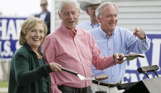 Former Sec. of State Hillary Rodham Clinton, former President Bill Clinton and U.S. Sen. Tom Harkin work the grill during Harkin's annual fundraising Steak Fry, Sunday, Sept. 14, 2014, in Indianola, Iowa. (AP Photo/Charlie Neibergall)