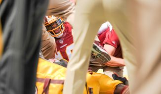 Washington Redskins quarterback Robert Griffin III (10) is attended to on the sideline after getting injured in the first quarteras the Washington Redskins play the Jacksonville Jaguars at FedExField, Landover, Md., Monday, September 9, 2013. (Andrew Harnik/The Washington Times)