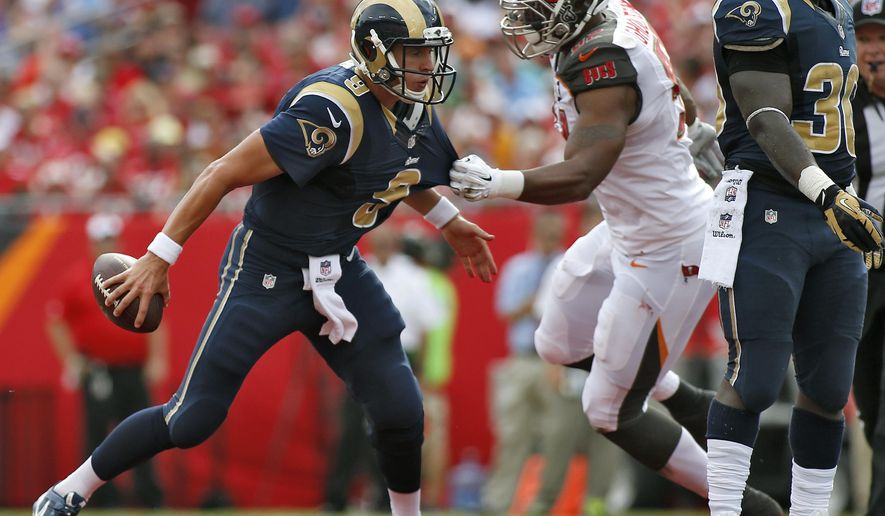 St. Louis Rams quarterback Austin Davis (9) tries to escape the grasp of Tampa Bay Buccaneers defensive end William Gholston (92) during the first quarter of an NFL football game Sunday, Sept. 14, 2014, in Tampa, Fla. (AP Photo/Brian Blanco)