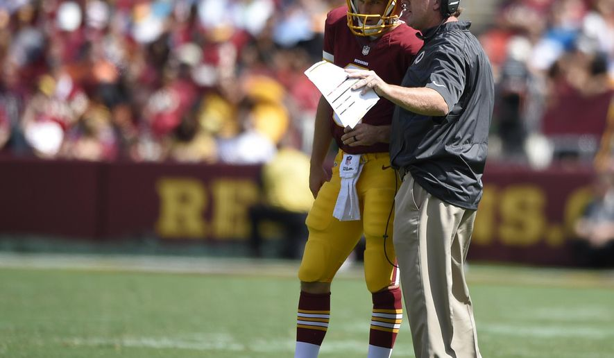 Washington Redskins quarterback Kirk Cousins (8) talks with head coach Jay Gruden during the first half of an NFL football game against the Jacksonville Jaguars, Sunday, Sept. 14, 2014, in Landover, Md. (AP Photo/Nick Wass)