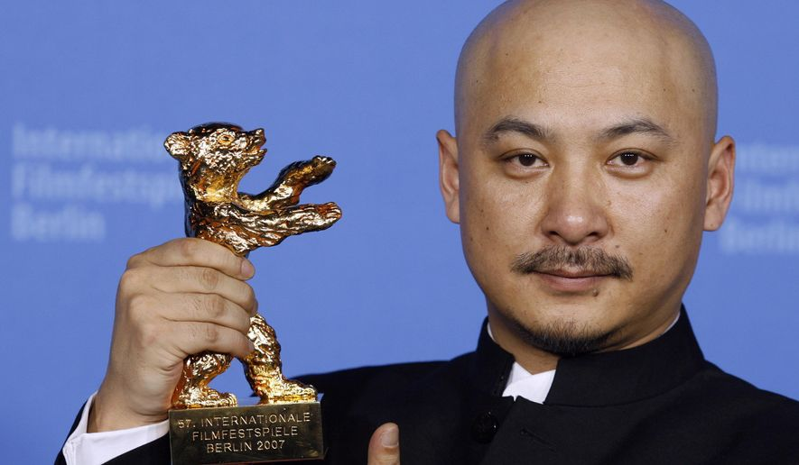 """File - In this Feb. 17, 2007 file photo, Chinese film director Wang Quan'an shows his Golden Bear award for the best movie at the 57th International Film Festival Berlin 'Berlinale' in Berlin for his movie """"Tuyas Marriage."""" Beijing police say they have detained Wang on a charge of prostitution. Police said in a statement Monday, Sept. 15, 2014 that Wang was found with a suspected prostitute several days ago in a Beijing apartment and paid the woman 800 yuan ($130) for the service. Police say Wang engaged in prostitution for three nights in a row. (AP Photo/Markus Schreiber, Pool, File)"""