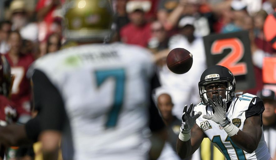 Jacksonville Jaguars wide receiver Marqise Lee (11) catches a pass from quarterback Chad Henne (7) during the second half of an NFL football game against the Washington Redskins, Sunday, Sept. 14, 2014, in Landover, Md. (AP Photo/Nick Wass)