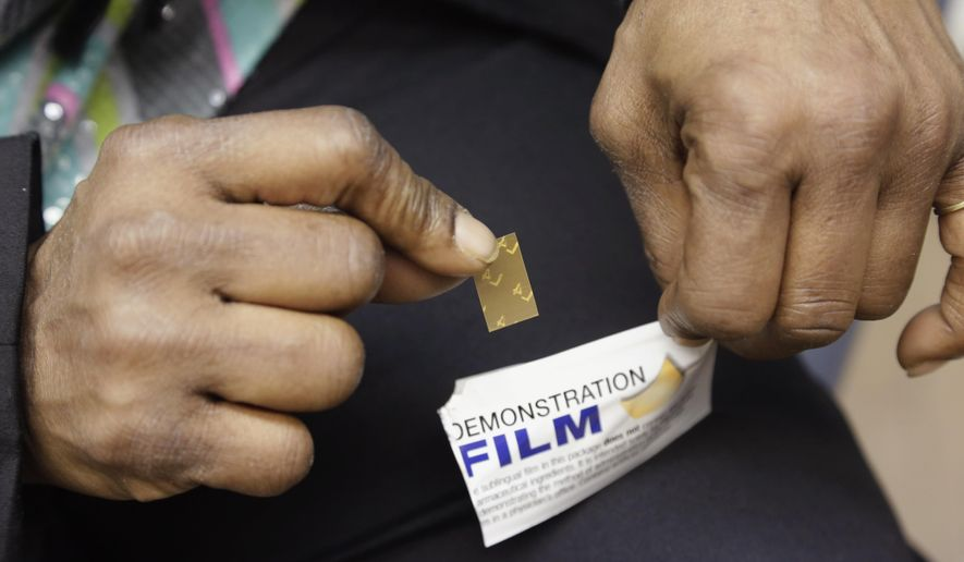 Shavonne Bullock, a recovering heroin addict, holds a demonstration dose of the medication Suboxone during an appointment at the West Division Family Health Center in Chicago on March 11, 2013. Each dose is incorporated on a dissolvable film, which is placed below the tongue where is dissolves and is absorbed into the bloodstream. Suboxone helps suppress withdrawal symptoms and reduce cravings for people recovering from addiction to opioid drugs. (Associated Press) **FILE**
