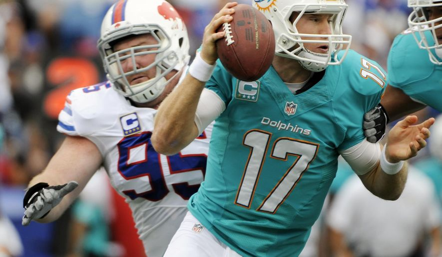 Miami Dolphins quarterback Ryan Tannehill (17) scrambles from Buffalo Bills defensive tackle Kyle Williams (95) during the first half of an NFL football game on Sunday, Sept. 14, 2014, in Orchard Park, N.Y. (AP Photo/Gary Wiepert)