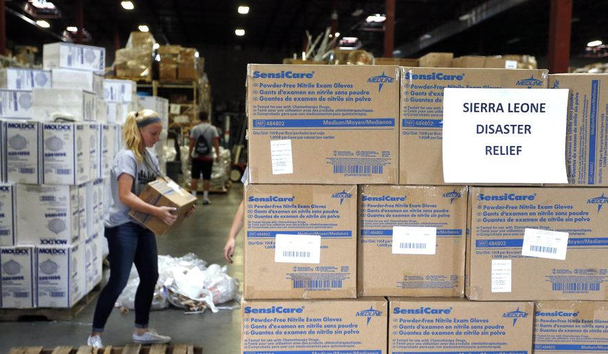 FILE - In this Sept. 9, 2014 file photo, Valor Christian High School sophomore and volunteer Paige Kula loads a pallet with medical supplies bound for Sierra Leone to combat Ebola, inside the warehouse of Project C.U.R.E., in Centennial, Colo. The US strategy in fighting Ebola is two-pronged: Step up efforts to deliver desperately needed supplies and people to West Africa, while making sure hospitals at home know what to do if someone travels here with the infection. In addition to shipments of hospital beds and protective suits, the government is taking unusual steps to encourage a variety of health care workers to volunteer to go to the outbreak zone _ and is offering some training before they head out. Here are questions and answers on the U.S. response. (AP Photo/Brennan Linsley, File)