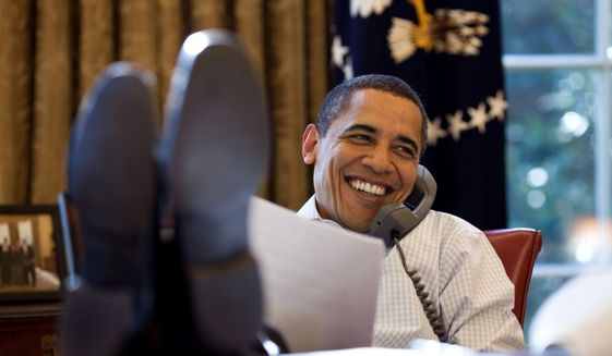 President Obama talks on the phone from the Oval Office in 2009. (White House photo)