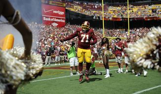 Washington Redskins tackle Trent Williams (71) runs out to the field during player introductions before an NFL football game against the Jacksonville Jaguars, Sunday, Sept. 14, 2014, in Landover, Md. (AP Photo/Nick Wass)