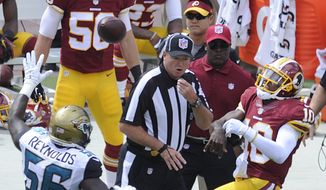 Washington Redskins quarterback Robert Griffin III (10) grimaces as he throws the ball after injuring his left ankle in the first quarter against the Jacksonville Jaguars at FedEx Field, Sept. 14, 2014. (Preston Keres/Special for The Washington Times)