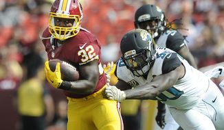 Washington Redskins running back Silas Redd (32) breaks away from Jacksonville Jaguars defensive end Andre Branch (90) during a fourth quarter run at FedEx Field, Sept. 14, 2014. (Preston Keres/Special for The Washington Times)