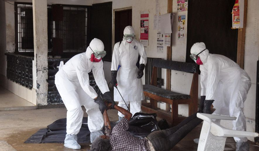 Health workers in protective gear move the  body of a person that they suspect dyed form the Ebola virus in Monrovia, Liberia, Tuesday, Sept. 16, 2014. The number of Ebola cases in West Africa could start doubling every three weeks and it could end up costing nearly $1 billion to contain the crisis, the World Health Organization warned Tuesday.  (AP Photo/Abbas Dulleh)