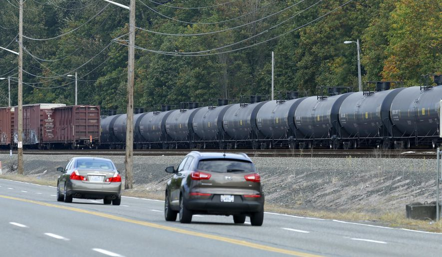 A long line of rail cars containing oil sit on tracks south of Seattle, Tuesday, Sept. 16, 2014. In a report to the Seattle City Council, city emergency planners say more must be done to lower the risk of a possible oil train accident and improve the city's ability to respond. (AP Photo/Ted S. Warren)