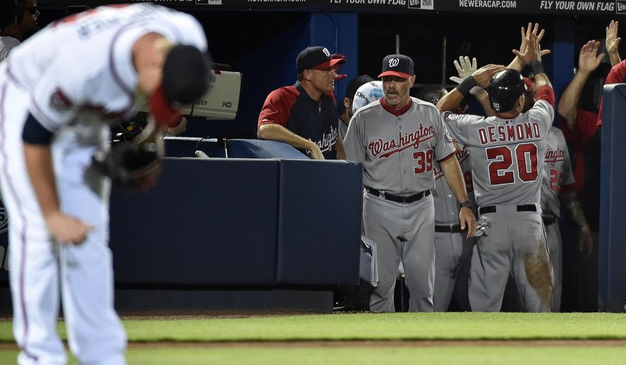 Washington Nationals' Ian Desmond (20) is congratulated in the dugout after scoring on a wild pitch by Atlanta Braves relief pitcher David Carpenter, left, during the ninth inning of a baseball game Tuesday, Sept. 16, 2014, in Atlanta. Washington won 3-0 to clench the NL East division. (AP Photo/David Tulis)
