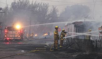 Firefighters work to put out fires and protect structures along Center Street Monday, Sept. 15, 2014, in Weed, Calif. (AP Photo/The Record Searchlight, Greg Barnette) ** FILE **