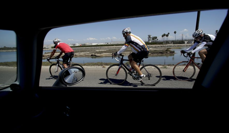 Bicyclists make their way down Pacific Coast Highway, Tuesday, Sept. 16, 2014, in Huntington Beach, Calif. Under statewide regulations taking effect Tuesday, drivers must give bikes a buffer zone of at least three feet while passing. (AP Photo/Chris Carlson)