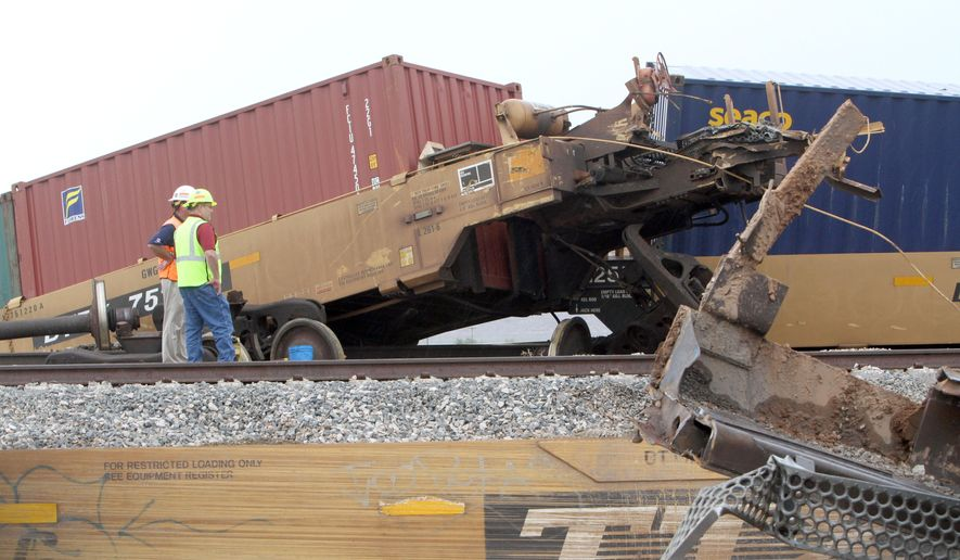 Crews work to remove 39 cars of a 179-car Union Pacific train that derailed approximately four miles south of Picacho, Arizona late September 15, 2014. According to Zoe Gisela Richmond, Director of Public Affairs for Union Pacific, an intense local thunderstorm with high winds may have played a part in the accident. (AP Photo/Casa Grande Dispatch, Steven King)