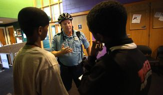 FILE - In this July 16, 2014 file photo Minneapolis police officer Mike Kirchen talks with Mohamed Salat, left, and Abdi Ali at a community center where members of the Somali community gather in Minneapolis. The nationwide effort to stop a new wave of Westerners being recruited by terror groups, this time for Islamic State militant groups in Syria and Iraq, could take some cues from Minnesota. Attorney General Eric Holder said Monday,  Sept. 15, 2014 the Justice Department is launching a series of pilot programs to help detect American extremists looking to join terror organizations in countries like Syria and Iraq. (AP Photo/The Star Tribune, Jim Gehrz, File)
