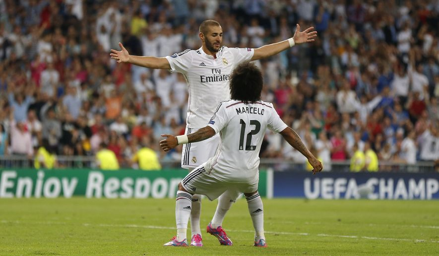 Real Madrid's Karim Benzema celebrates with Real Madrid's Marcelo after scoring his side's fifth goal during the Champions League Group B soccer match between Real Madrid and Basel at the Santiago Bernabeu stadium in Madrid, Spain, Tuesday Sept. 16, 2014. (AP Photo/Daniel Ochoa de Olza)
