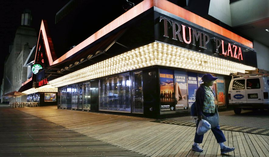 Burned out lights can be seen as a woman passes Trump Plaza Hotel & Casino on The Boardwalk early Tuesday, Sept. 16, 2014, in Atlantic City, N.J. Trump Plaza Hotel & Casino closed Tuesday. Trump Plaza is the fourth Atlantic City casino to go out of business so far this year. (AP Photo/Mel Evans)