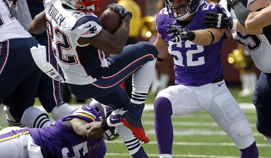 New England Patriots running back Stevan Ridley (22) carries the ball as Minnesota Vikings linebacker Jasper Brinkley and linebacker Chad Greenway (52) defend during the first quarter of an NFL football game Sunday, Sept. 14, 2014, in Minneapolis. (AP Photo/Ann Heisenfelt)