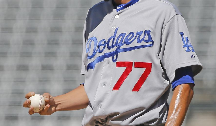 Los Angeles Dodgers starting pitcher Carlos Frias reacts after giving up a three-run home run to Colorado Rockies' Justin Morneau during the first inning of a baseball game Wednesday, Sept. 17, 2014, in Denver. (AP Photo/Jack Dempsey)