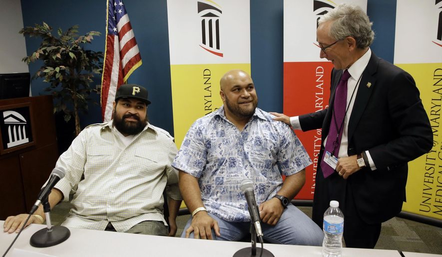 Chris Kemoeatu, left, and his brother Ma'ake chat with Dr.  Matthew Weir after a news conference at the University of Maryland Medical Center, Wednesday, Sept. 17, 2014, in Baltimore. Chris Kemoeatu's football career was cut short after seven seasons with the Pittsburgh Steelers when he learned he'd need a kidney transplant. That's when his older brother, a 99-percent kidney match and a former nose tackle for the Baltimore Ravens, stepped in, and left the Ravens in 2012. Weir was part of the team that performed the transplant in August, and the brothers are now recovering from their surgeries. (AP Photo/Patrick Semansky)