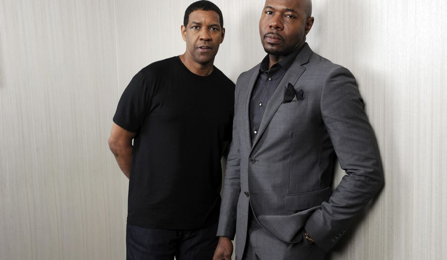 """In this Sept. 7, 2014 photo, Denzel Washington, left, star of the film """"The Equalizer,"""" poses with the film's director Antoine Fuqua at the Four Seasons Hotel during the 2014 Toronto International Film Festival in Toronto. (Photo by Chris Pizzello/Invision/AP)"""