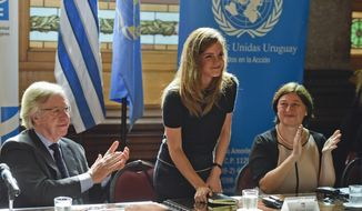 Uruguay's Vice President Danilo Astori, left, and Director of U.N. Women Gulden Turkoz, right, applaud after a speech by Emma Watson, U.N. Women Goodwill Ambassador, at Parliament in Montevideo, Uruguay, in this Wednesday, Sept. 17, 2014, file photo. (AP Photo/Matilde Campodonico)