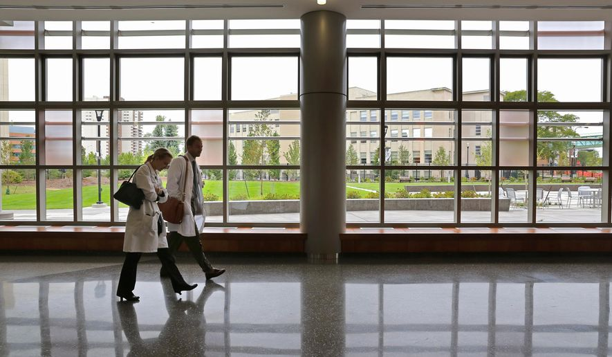 Two people walk toward the South Street exit of the new Western Michigan University Homer Stryker M.D. School of Medicine in Kalamazoo, Mich. The state-of-the-art facility is already in use: 54 medical students and 200 residents began their studies in August. (AP Photo/Kalamazoo Gazette-MLive Media Group, Mark Bugnaski) ALL LOCAL TELEVISION OUT; LOCAL TELEVISION INTERNET OUT