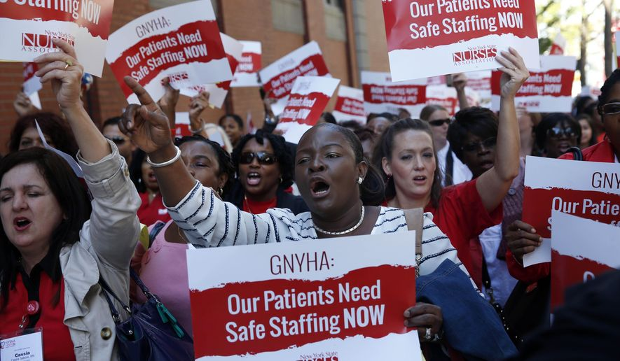 Nurses, doctors and other health care workers rally outside the offices of the Greater New York Hospital Association in New York, Wednesday, Sept. 17, 2014.  The demonstrators are backing a bill in the state legislature that would set minimum staffing levels for hospital nurses. The hospital association does not support the legislation.  (AP Photo/Seth Wenig)
