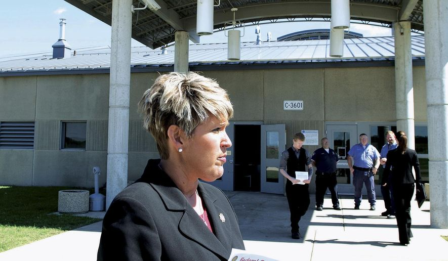 In this Tuesday, Sept. 16, 2014 photo, Beth Pottios, regional public informational officer for the Federal Bureau of Prisons, stands outside the Thomson Correctional Center in Thomson, Ill., during a three-day job fair. Hundreds of applicants, some from as far away as Kentucky and Minnesota, have come to the Mississippi River town to apply for federal prison jobs. The state of Illinois built the Thomson prison in 2001, but budget troubles kept it from fully opening. The federal government bought it in 2012 for $165 million. More than 1,000 jobs will be brought to the Thomson area through the first phase of hiring. (AP Photo/Sauk Valley Media, Alex T. Paschal)