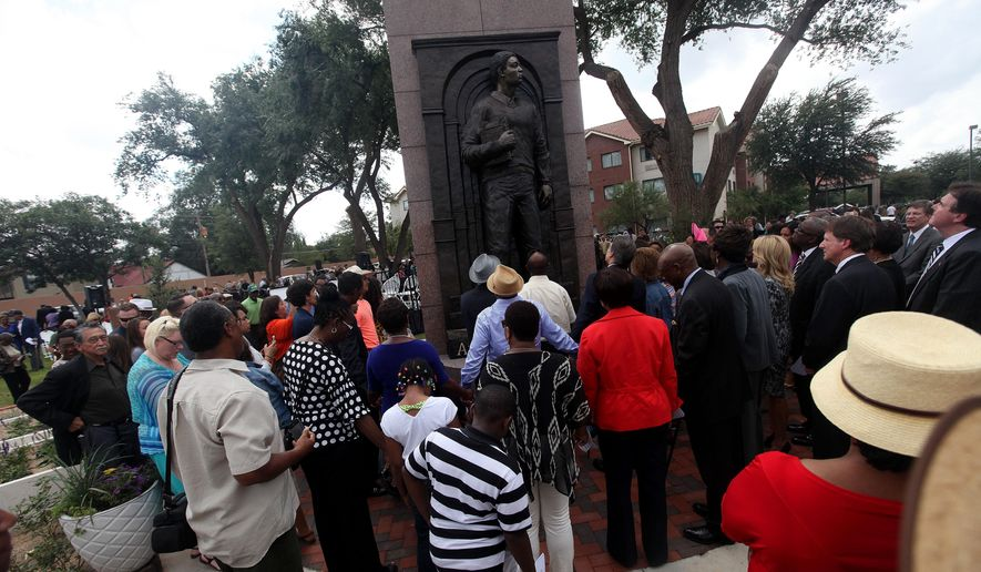 A statue of Timothy Cole is unveiled during a ceremony in Lubbock, Texas, Wednesday, Sept. 17, 2014. Twenty-eight years to the day after Timothy Cole was falsely convicted of raping a Texas Tech student, Lubbock and state officials unveiled a statue honoring the U.S. Army veteran on a street corner not far from where the victim was abducted. (AP Photo/Lubbock Avalanche-Journal, Zach Long)