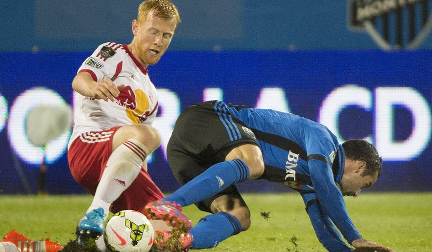 Montreal Impact's Andres Romero, right, and New York Red Bulls' Richard Eckersley battle for the ball during the first half of a CONCACAF Champions League soccer game, Wednesday, Sept. 17, 2014  in Montreal, (AP Photo/The Canadian Press, Graham Hughes)
