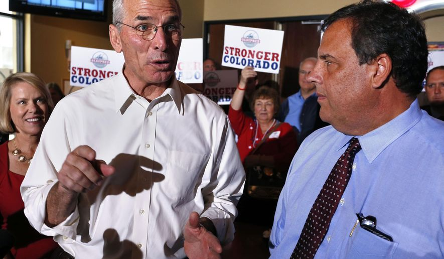 FILE - In this July 23, 2014 file photo, GOP gubernatorial candidate Bob Beauprez, left, gestures while he and visiting New Jersey Gov. Chris Christie, right, make a campaign stop at diner in Denver. According to a poll released Wednesday Sept. 17, 2014, Beauprez has jumped ahead of Colorado Democratic Gov. John Hickenlooper by 10 points, placing the incumbent behind by a substantial margin for the first time in the race. (AP Photo/Brennan Linsley, file)