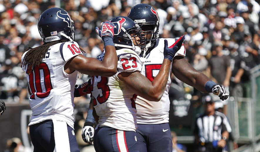 Houston Texans running back Arian Foster, center, celebrates after scoring a touchdown on a 5-yard run with teammates DeAndre Hopkins, left, and Derek Newton, right, in the first quarter of an NFL football game Sunday, Sept. 14, 2014, in Oakland, Calif. (AP Photo/Beck Diefenbach)